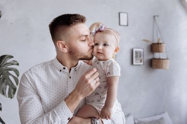 dad is kissing and hugging his child daughter. happy...