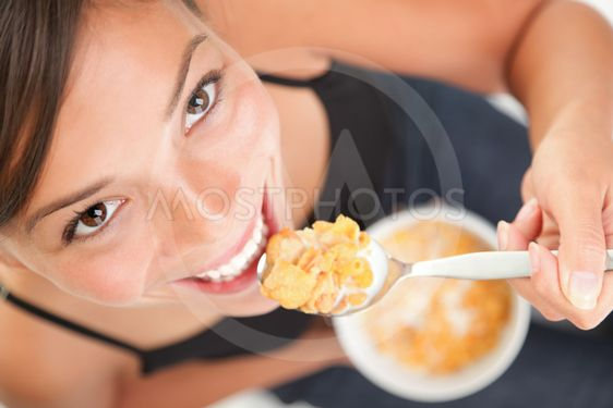 Kvinna äter majsflingor Corn flakes spannmål