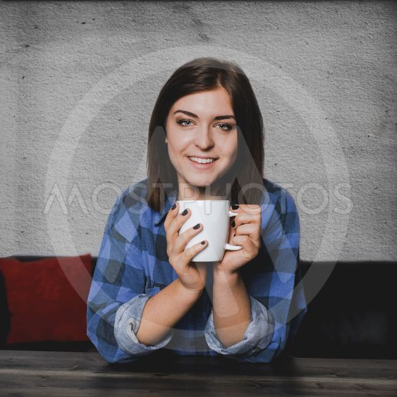 Young woman sitting at a table with a coffee mug