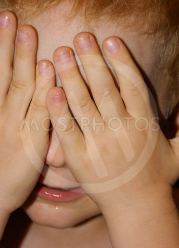 Little red-haired boy covered his hands with his hands,...