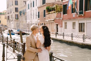 Italy wedding in Venice. Newlyweds stand embracing on...
