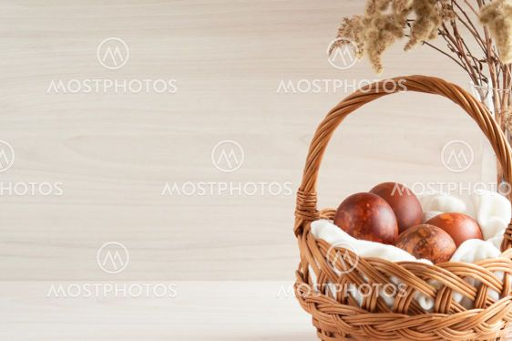 Easter eggs painted with natural dyes in a wicker...