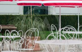 metallic chairs and white and red umbrella in...