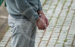 hands of man handcuffed in the street