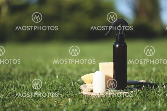 Spray bottle on the wooden plate with brush and soap