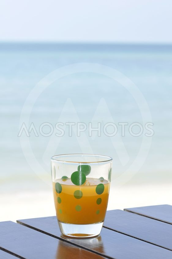 Glass of orange juice at the beach