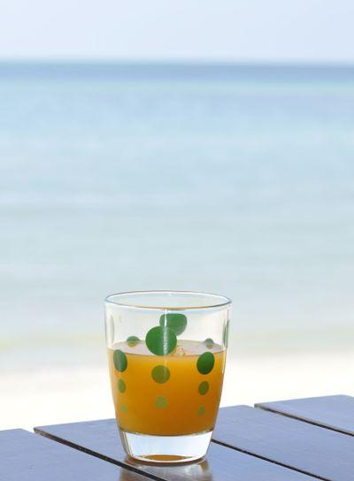 Glass of orange juice at the beach