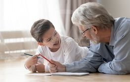 Happy boy have fun drawing at home with grandfather