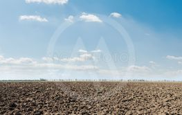 black plowed field and blue sky with clouds