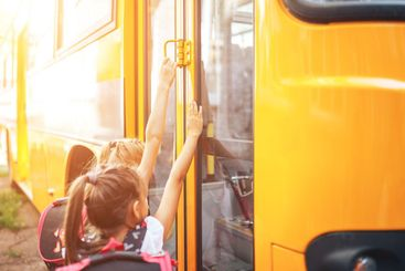Schoolgirls with backpacks enter the school bus, back to...