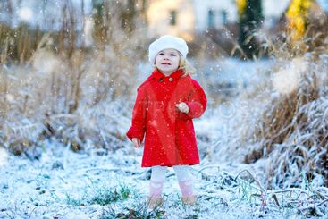 Outdoor winter portrait of little cute toddler girl in...