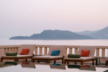 Wooden loungers near the pool at the villa by the sea,...