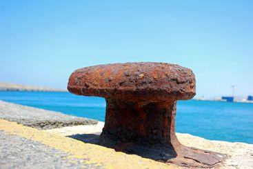 Rusty wide capstan in harbor