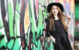 Young beautiful girl in a hat and with a dark make-up...