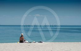 woman in swimsuit and hat sitting on the...