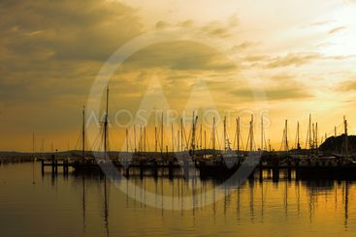 Docked yachts in marina at sunset