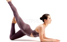 Beautiful young woman doing yoga or pilates exercise,...