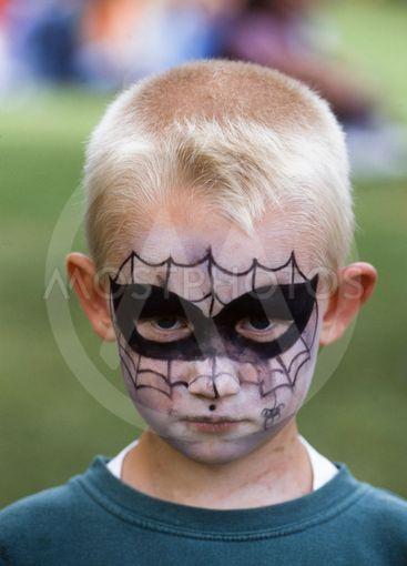 En pojke med ansiktsmålning som spindelmannen,...