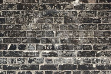 Old weathered black brick wall texture close up.