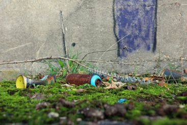 Rusty spray cans on mossy ground in front of a wall