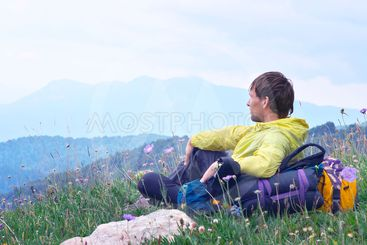 Young Man Traveller with backpack sitting on grass with...
