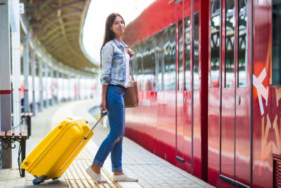 Young girl with luggage on the platform waiting for...