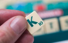 plastic letters K in hand on Scrabble board game
