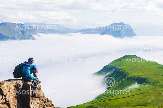 Hiker sitting on cliff, Mykines, Faroe Islands