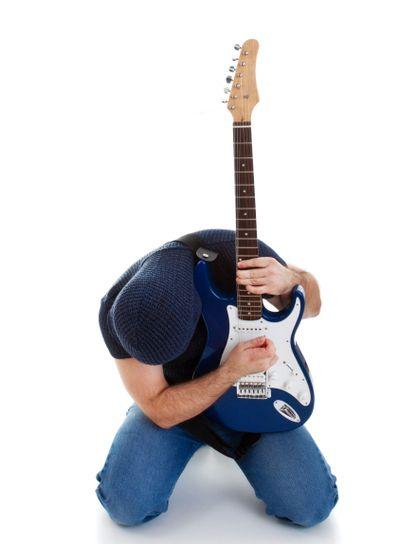 rocker playing guitar kneeling