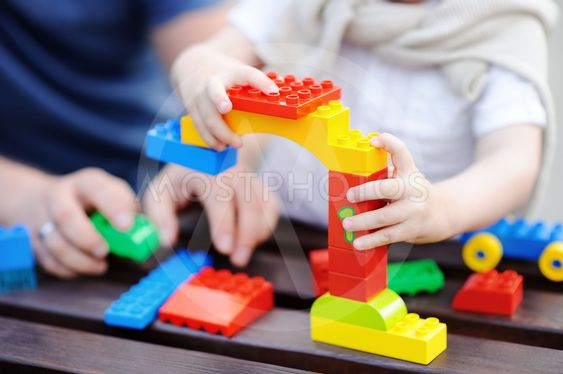 Father with his toddler son playing with colorful plastic...