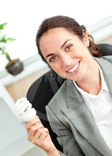Bright hispanic businesswoman holding a light bulb...