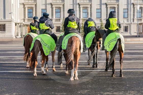 Female mounted police on horse back at the city street