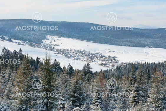 village in valley between winter mountains