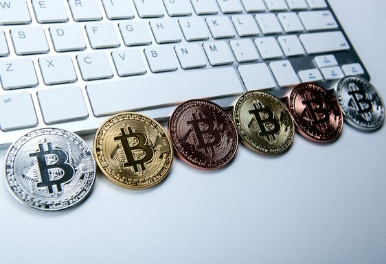 six coins of bitcoin on white laptop pc keyboard
