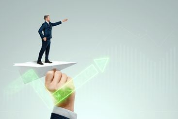 Startup. Businessman flying on a paper airplane with the...