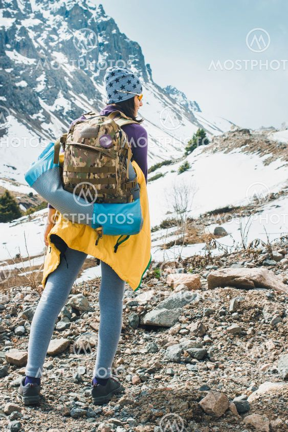 Traveling girl with backpack hiking in the mountains,...