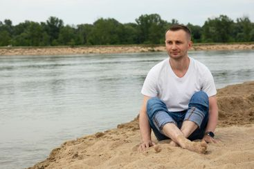 Lonely positive man sitting on the beach river