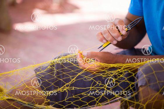 Fisherman repairing fishing net
