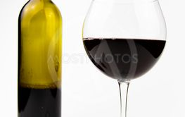 Glass of wine and a bottle on a gray background.