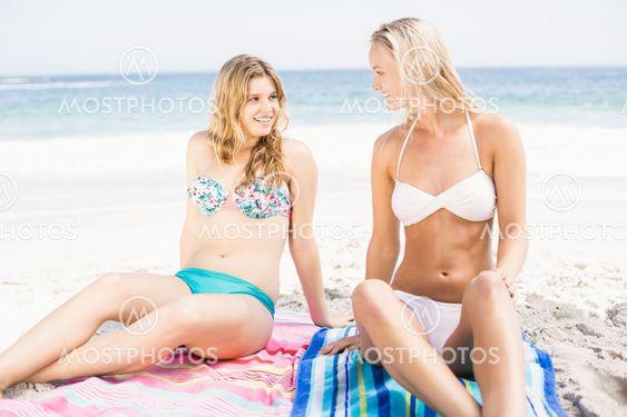Pretty women in bikini sitting and talking on the beach