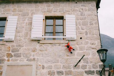 Toy Santa Claus climbs through a white window with...