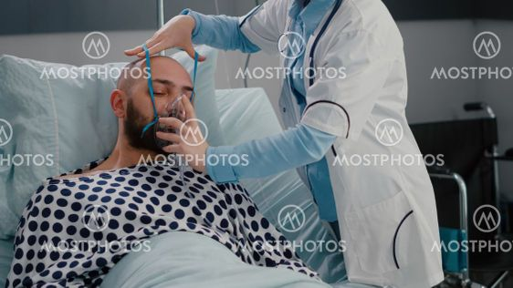 Patient sitting in bed while woman doctor putting oxygen...