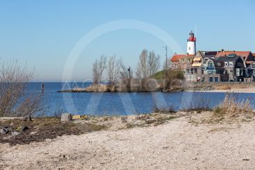 Beach of former island Urk with view at historic Lighthouse