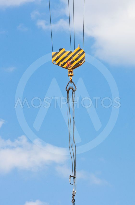Crane hook over blue sky with clouds