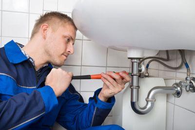 Male Plumber Fixing Sink In Bathroom