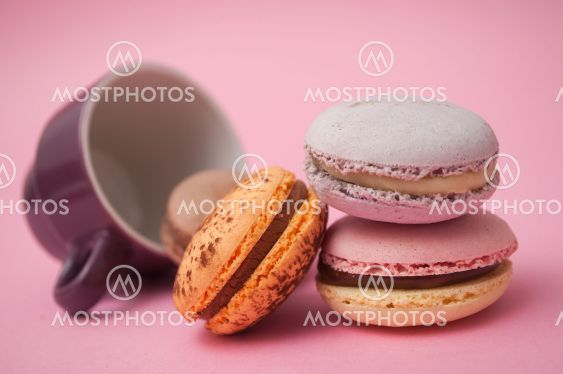 french macarons and cup of coffee on pink background