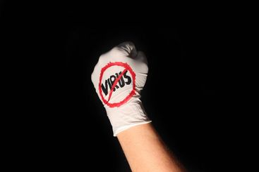 Fist in disposable glove with anti virus sign in front...