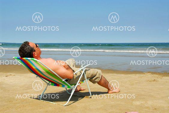 Mies, rentouttava rannalla