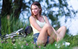 Pretty young woman with bicycle on a summer day in green...
