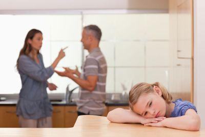 Sad little girl listening her parents having an argument